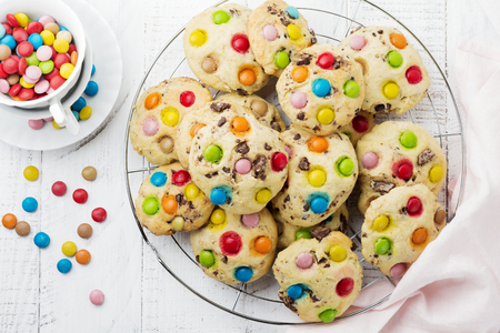 Children's cookies with colorful chocolate sweets in sugar glaze on white wooden background. Selective focus. Top view. Place for text. Foto de archivo