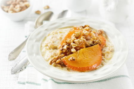 Oatmeal porridge with caramelized persimmon and walnuts in a light ceramic bowl on a white wooden background. Selective focus. Top view. Copy space. Stock Photo