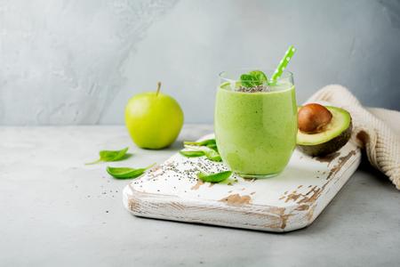 Frullato verde sano vegetariano da semi di avocado, foglie di spinaci, mela e chia su sfondo grigio cemento. Messa a fuoco selettiva. Spazio per il testo.