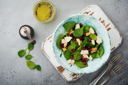 Fresh useful vegetarian wholesome spinach, pomegranate seeds, walnut, saffron, pepper and ricotta salad on gray background.