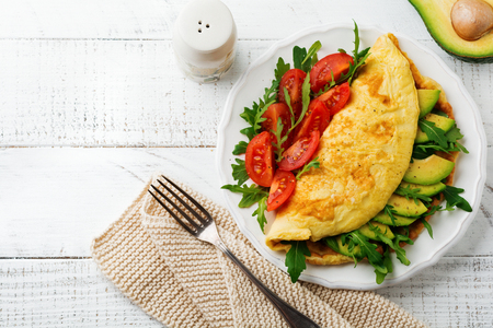 Omelette with avocado, tomatoes and arugula on white ceramic plate on light stone background. Healthy breakfast. Selective focus. Top view. Copy space. Stock Photo