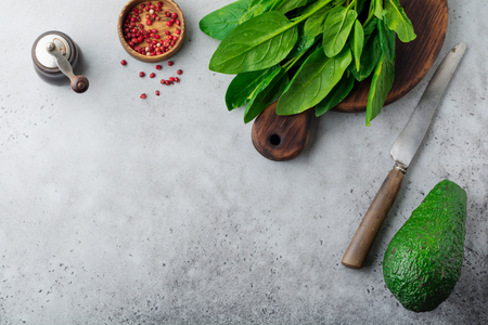 Fresh raw spinach leaves on a wooden rustic stand on a gray old concrete background. Ingredients for salad. Selective focus. Top view. Copy space. Stock Photo