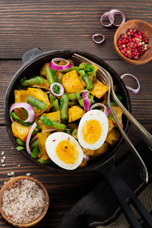 Warm potato salad with green beans, pepper, parsley, eggs and red onion in frying pan on old wooden background. Selective focus. Top view. Copy space.
