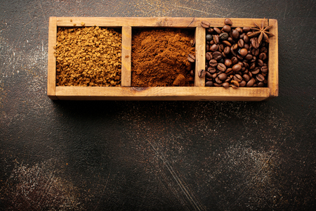 Food background with three kinds of coffee: beans, milled, instant in wooden box on old concrete brown background. Rustic stile. Selective focus. Top view. Stock fotó