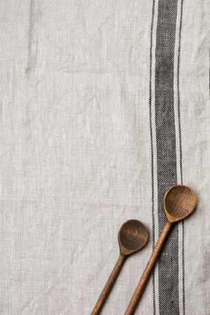 Texture of gray fabric with brown stripe and two wooden old vintage spoons. Top view with copy space.