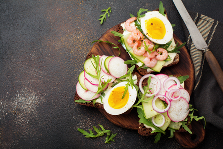 Open sandwiches on dark rye bread with eggs, shrimps, radishes, cucumber, cream cheese and arugula for breakfast on old dark background. Smorrebrod Traditional dish of Danish cuisine. Top view.