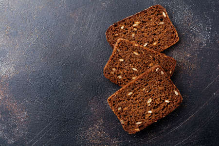 Three pieces of rye bread with sunflower seeds for sandwiches on stand. Top view.
