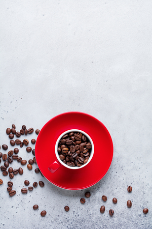 Red Cup with coffee beans inside on gray concrete background. Top view.