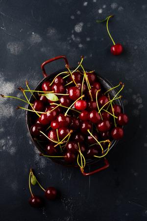 Fresh berries of cherries in black ceramic plate on dark concrete old background. Top view.