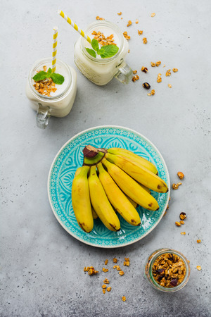 Banana smoothie with granola, dried fruits and mint on gray concrete background. Top view.