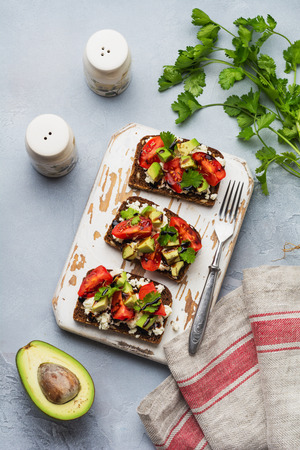 Avocados, cherry tomatoes and feta cheese sandwiches with balsamic sauce and cilantro on old olive board. Top view. Stockfoto