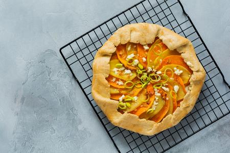 Pumpkin, potato, feta cheese and leek galette pie plate on gray concrete table background. Top view.l
