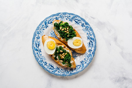Fried spinach, egg and pine nuts sandwiches on light background. Delicious healthy breakfast or snack. Top view.