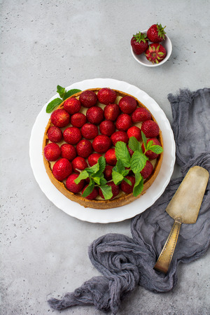 Cheesecake with fresh strawberries and mint on white plate on gray concrete background. Top view. Banco de Imagens