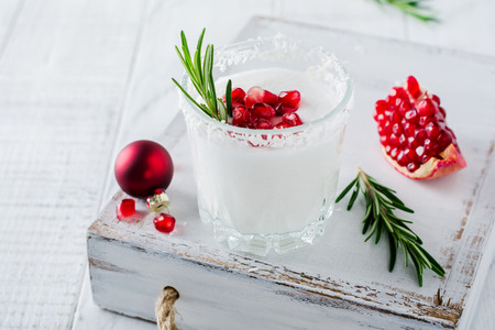 Christmas coconut punch with pomegranate seeds and sprigs of rosemary on light background. Selective fоcusе. Top view.