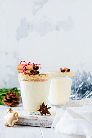 Eggnog Traditional Christmas drink milkshake with cinnamon on light old background. Selective focus. Stock Photo