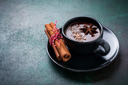 Hot chocolate with anise and nuts in black ceramic cup on old dark green concrete background. Selective focus. Standard-Bild