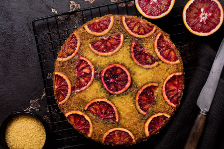 Upside down blood orange cake on old dark concrete background. Rustic stile. Selective focus