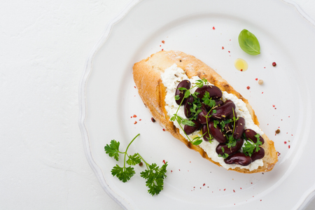 Sandwich with red beans, garlic, olive oil and curd cheese on white background. Mexican Cuisine. Top view.