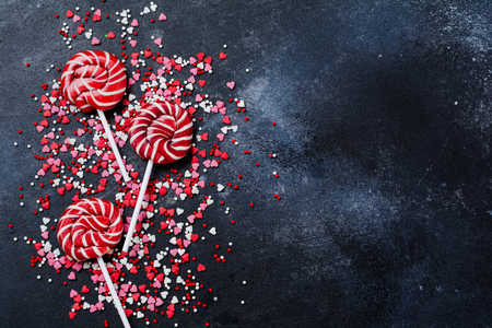 Colorful candies and lollipops over dark old concrete background. Top view with copy space.