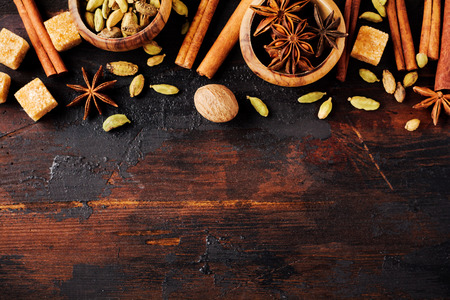 Set of spices of star anise, cardamom, cinnamon and brown sugar on old wooden background. Flat lay