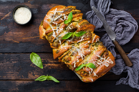 Pull-apart bread with Italian pasta pesto, basil and parmesan cheese in baking form over old wooden background. Top view. Rustic stile.
