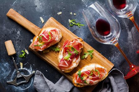 Offene Schinkensandwiches, Rucola und Hartkäse, serviert auf Holzständer mit einem Glas Rotwein auf altem dunklem Betonhintergrund. Rustikaler Stil. Ansicht von oben. Standard-Bild