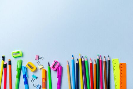 Notebook, colored pencils, ruler, pen, eraser, sharpener and more. School and office stationery on blue background. Concept back to school. Top view.