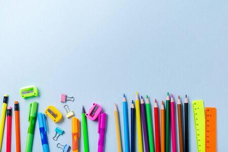 Taccuino, matite colorate, righello, penna, gomma, temperino e altro ancora. Scuola e cancelleria per ufficio su sfondo blu. Concetto di ritorno a scuola. Vista dall'alto.