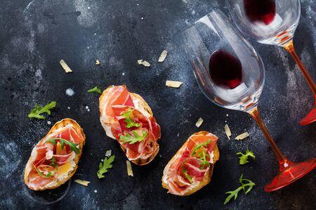 Offene Schinkensandwiches, Rucola und Hartkäse, serviert auf einem Holzständer mit einem Glas Rotwein auf einem konkreten alten dunklen Hintergrund. Rustikaler Stil. Ansicht von oben.
