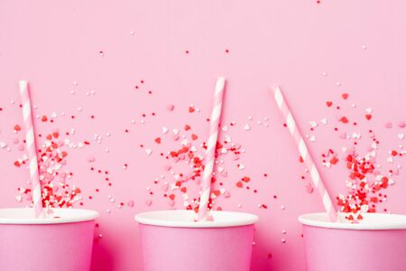 Three pink paper cup of coffee on pink paper light background. Zero waste concept. Flat lay.