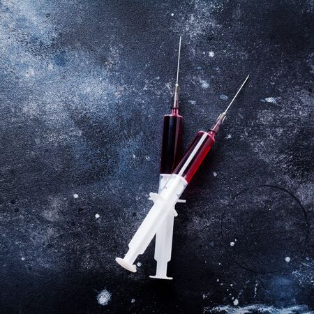 Syringe with blood on old concrete background. Square image. Top view.