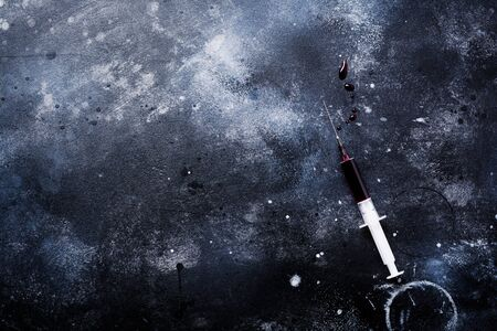 Syringe with blood on old concrete background. Top view.