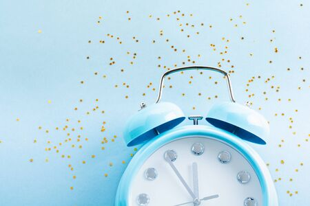 Big blue alarm clock lying and surface showing 23 hours 55 minutes with shiny confetti stars on light blue surface background. Top view.