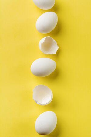 Weiße rohe Hühnereier, die in vertikaler Reihe mit zerbrochenem Ei auf gelbem Hintergrund liegen. Ansicht von oben.