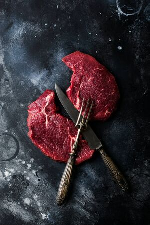 Two Raw beef steak with spices, onions and chili on dark slate or concrete background. Top view