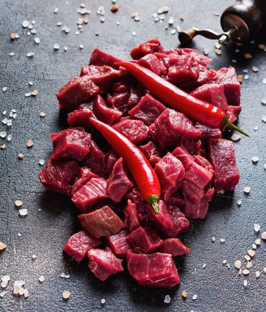 Cut beef into small pieces with sea salt, dried herbs and chili peppers on dark slate or concrete   background. Top view.