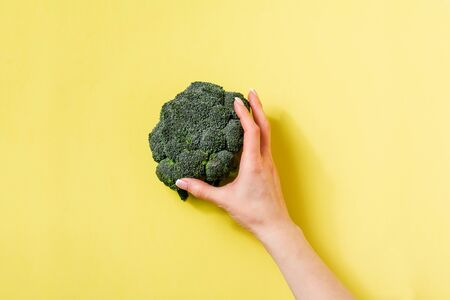 Female hand holds one fresh green broccoli lying on yellow light background. Top view. 版權商用圖片