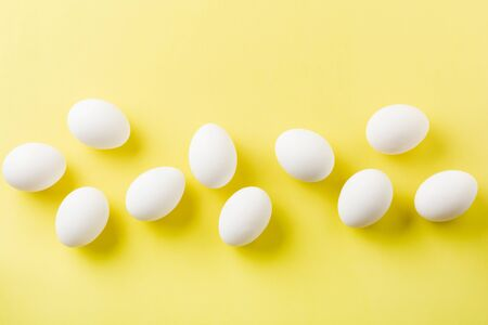 White raw chicken eggs lying in horizontal row with broken egg on yellow background. Top view.