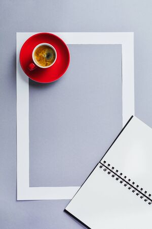 Notebook or sketchbook, red cup with coffee and paper frame on classic blue background. Morning minimal concept.