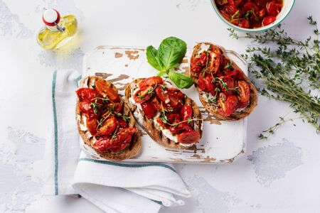 Sandwiches with baked cherry tomatoes and cottage cheese, thyme, garlic and herbs on an old light vintage background. Top view.  Zdjęcie Seryjne
