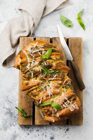 Pull-apart bread with Italian pasta pesto, basil and parmesan cheese in baking form over old light concrete background. Top view. Rustic stile.