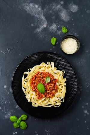 Traditional Italian dish fettuccine pasta with bolognese sauce, basil and parmesan cheese in black plate on dark wooden background. Top view. Banco de Imagens - 138550799
