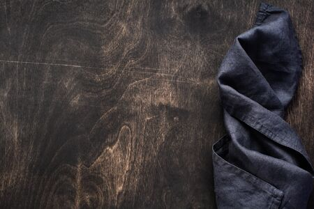 Dark brown wood texture with cotton kitchen napkin or towel over  . Abstract background.Copy space background.