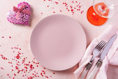 Valentines day table setting with pink plate and gift heart on pink light background. Banque d'images - 140642898