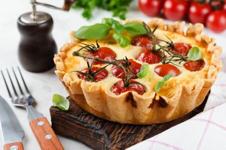 Homemade quiche tart with cherry tomatoes, basil, seasonings and cheese on white stone background. Selective focus.