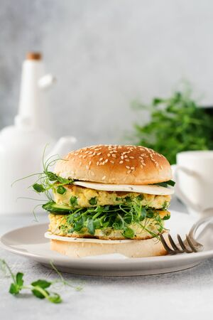 Healthy Vegetarian burger with egg and pea shoots and seeds microgreen, fresh salad, cucumber slice on a cutting wooden board on light background. Selective focus.