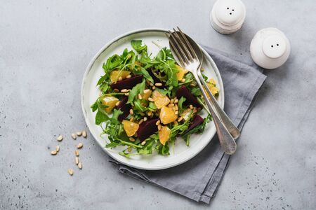Beets, orange, pine nut, olive oil, feta cheese and arugula salad in ceramic plate on old concrete table background. Top view.