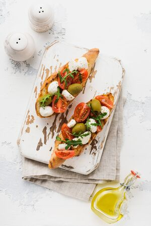 Caprese bruschetta toasts with cherry tomatoes, mozzarella, olives and basil on white plate old light background. Top view.
