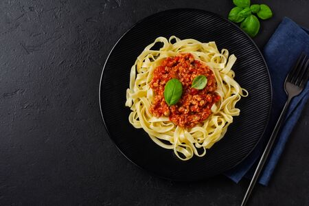 Traditional Italian dish fettuccine pasta with bolognese sauce, basil and parmesan cheese in black plate on dark wooden background. Top view.